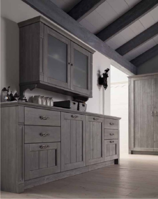 Le basi della cucina, sovrastate da elementi pensili a vetrina ...